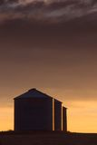 Sidelit Bins. Warm sunset light reflects from the side of agricultural storage bins stock image