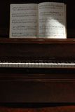Sidelit piano with music. A sidelit old piano with music Stock Images