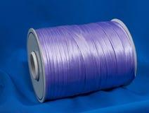 Siden- flätad tråd för lavendel för att sy på blått tyg sammansättning royaltyfri fotografi