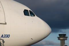 Sideshot di Airbus 330 della cabina di pilotaggio con la torre di controllo e delle nuvole nei precedenti Immagine Stock Libera da Diritti