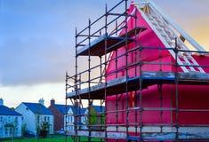 Sideview του καινούργιου σπιτιού κάτω από την κατασκευή με το κόκκινο προστατευτικό στρώμα, το ικρίωμα, την ξυλεία και τους ξύλιν Στοκ φωτογραφία με δικαίωμα ελεύθερης χρήσης