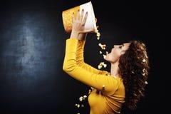 Sideview красивой женщины лить притворный попкорн от ведра Стоковое Изображение