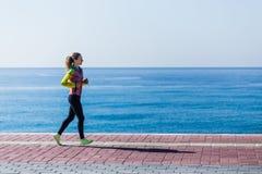 Sideview молодой женщины бежать взморьем Стоковая Фотография