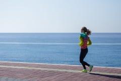 Sideview молодой женщины бежать взморьем стоковое фото rf