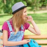 Sideview усмехаясь девушки на стенде ` s парка Стоковая Фотография RF