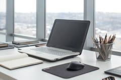 Sideview av kontorsskrivbordet med den tomma bärbara datorn och olika hjälpmedel Arkivfoton