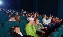 Sideview av pojkar som håller ögonen på film i bion royaltyfri fotografi