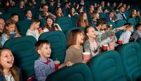 Sideview av roliga barn som håller ögonen på film i bion Fotografering för Bildbyråer