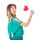 Sideview of beautiful woman holding red heart-shaped lollypop in front of her body stock photos