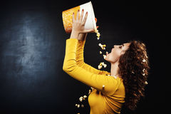 Sideview of beautiful woman pouring cheesy popcorn from bucket. Sideview of beautiful curly woman pouring cheesy popcorn from big popcorn bucket. Tasty snacks Stock Image