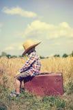 Sideview chłopiec obsiadanie na starej walizce wewnątrz Obrazy Royalty Free