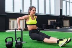 Sideview de fazer desportivo da mulher l-senta exercícios com as barras no gym imagem de stock royalty free