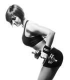 Sideview de la femme rousse d'ajustement faisant l'haltère incurvée t de deux-bras Images stock