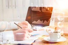 Sideview de la mesa con los gráficos del dibujo del hombre de negocios en cuaderno Imagen de archivo libre de regalías