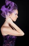 Sideview de la mujer joven hermosa en el sombrero violeta imagen de archivo libre de regalías