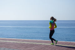 Sideview de la mujer joven que corre por la playa Foto de archivo libre de regalías