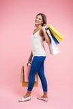 Sideview de la mujer joven sonriente que camina con los panieres coloridos Fotos de archivo