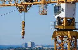 Sideview de la polea del gancho de la cabina de la grúa de construcción con la ciudad b aéreo Foto de archivo