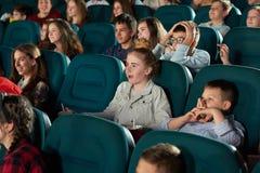 Sideview de niños de risa en el cine Imágenes de archivo libres de regalías