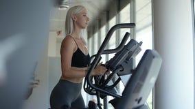 Sideview de uma menina loura no sportswear que exercita no instrutor elíptico no gym brilhante, vazio com janelas panorâmicos len vídeos de arquivo
