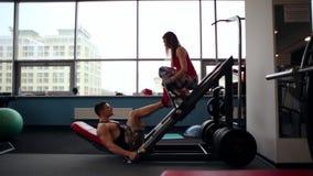 Sideview de un atleta de sexo masculino que hace ejercicio de la prensa de la pierna, resolviéndose en un gimnasio Una mujer atlé metrajes