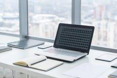 Sideview del desktop dell'ufficio con il computer portatile in bianco ed i vari strumenti Fotografia Stock Libera da Diritti