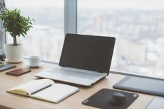 Sideview del desktop dell'ufficio con il computer portatile in bianco ed i vari strumenti Immagini Stock