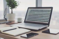 Sideview del desktop dell'ufficio con il computer portatile in bianco ed i vari strumenti Immagine Stock Libera da Diritti