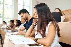 Sideview del estudiante joven prepearing para los exámenes en universidad foto de archivo libre de regalías