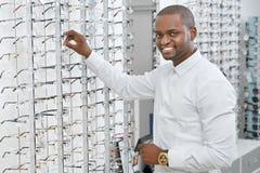 Sideview dell'uomo sorridente sta scegliendo gli occhiali in negozio ottico fotografia stock libera da diritti