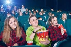 Sideview delle ragazze e del ragazzo che mangiano popcorn guardando film Fotografia Stock Libera da Diritti