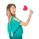 Sideview der Schönheit rotes Herz-förmiges lollypop vor ihrem Körper halten Stockfotos