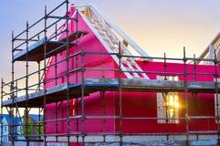 Sideview des neuen Hauses im Bau mit roter Schutzschicht, Gestell, Bauholz und hölzernen Brettern Lizenzfreie Stockfotografie