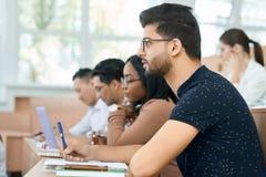 Sideview do estudante árabe que senta-se na universidade fotografia de stock