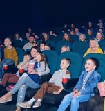 Sideview of happy children watching movie. Sideview of happy children watching interesting, funny movie, sitting on comfortable green places. Boys and girls Stock Photo