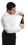 Sideview man or waiter opening bottle of champagne. A man, bartender or waiter opens a bottle of champagne, sparkling wine.  He is untwisting the metal cage Royalty Free Stock Photo