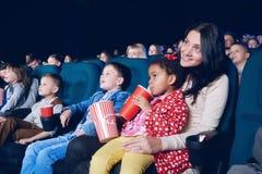 Sideview matki i córki dopatrywania film w kinie obraz royalty free