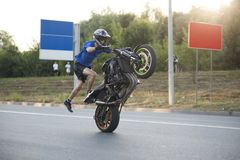 Sideview of moving biker making extremely dangerous stunt. Ivano-Frankivsk, Ukraine - 9 August 2015: Sideview of moving biker making extremely dangerous stunt Stock Photos