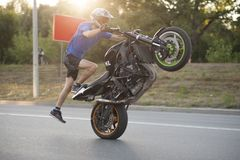 Sideview of moving biker riding on one wheel. Royalty Free Stock Image