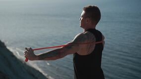 Muscular man with tattoo trains with fitness elastic bands outdoor with sea view