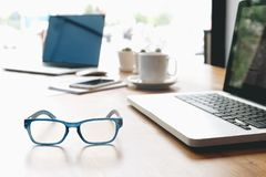 Sideview of office desk with laptop, glasses and other items royalty free stock image