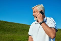 Sideview of old man talking on cellphone while summer day. Wearing white polo shirt with dark blue stripes. Looking at side. Having sportwatch on left hand Royalty Free Stock Photo