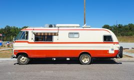 Sideview of Orange and White Travco Elite Motorhome. Stock Image