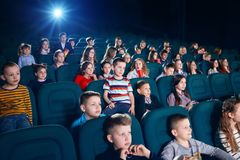Sideview of people watching movie in the cinema hall. Sideview of children watching movie in the cinema hall. Kids are very emotional, exited and satisfied stock photo
