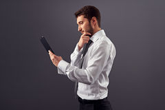 Thoughtful businessman with tablet pc Royalty Free Stock Image