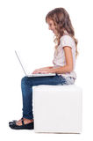 Sideview of smiley girl with laptop Royalty Free Stock Image
