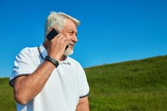 Sideview of sportsman talking on cellphone while sunny day. Wearing white polo shirt with dark blue stripes. Looking at side. Having sportwatch on left hand Stock Images