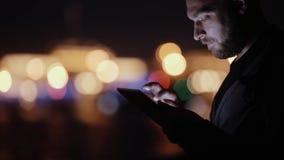 Sideview van een knappe mens, die neigend, gebruikend zijn tablet bij nacht glimlachen De vage Lichten van de Stad Moderne techno stock video
