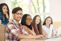 Sideview van groupmates die camerazitting bekijken op universiteit Stock Afbeelding