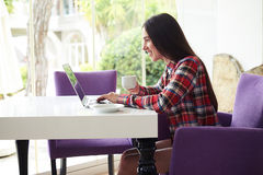 Sideview of young attractive woman typing on laptop on terrace Stock Photography